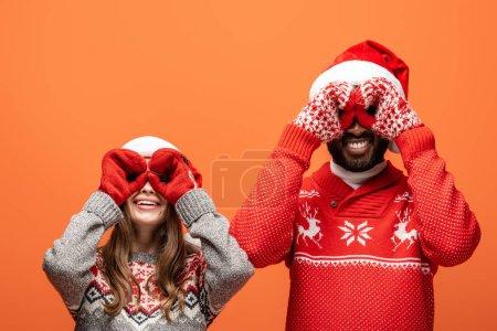 Photo pour Heureux couple interracial dans santa chapeaux, mitaines et pulls de Noël imitant jumelles avec les mains sur fond orange - image libre de droit