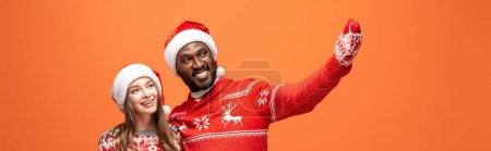 Photo pour Heureux couple interracial dans santa chapeaux, mitaines et pulls de Noël étreignant et pointant avec la main sur fond orange, vue panoramique - image libre de droit