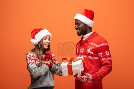 Photo pour Homme afro-américain cadeau de Noël cadeau à petite amie heureuse sur fond orange - image libre de droit