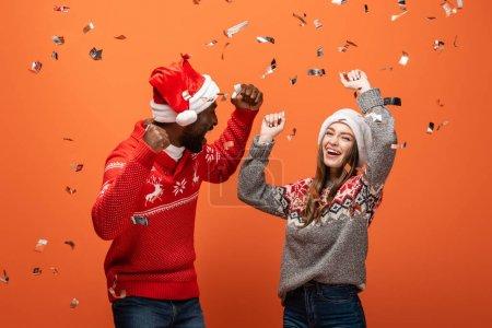 Photo pour Heureux couple interracial dans santa chapeaux et chandails de Noël montrant oui gestes sous confettis sur fond orange - image libre de droit