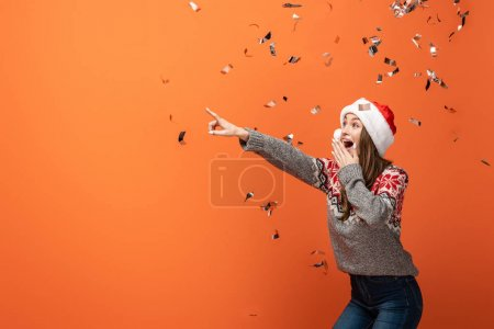 Photo for Surprised woman in santa hat under falling confetti pointing with finger away on orange background - Royalty Free Image