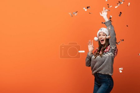 Photo for Happy woman in santa hat under falling confetti on orange background - Royalty Free Image