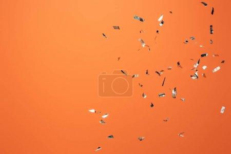 Photo pour Confettis argenté brillant sur fond orange - image libre de droit