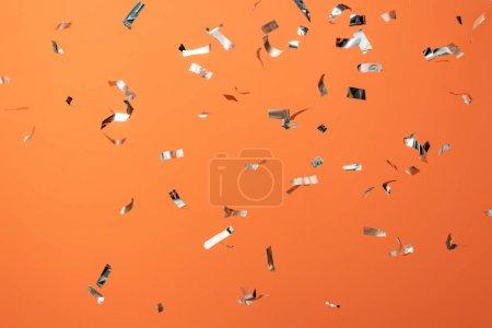 Photo pour Confettis argentés brillants sur fond orange - image libre de droit