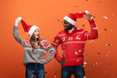 Photo pour Heureux couple interracial dans santa chapeaux et chandails de Noël en regardant les uns les autres sous confettis sur fond orange - image libre de droit