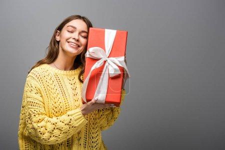 Photo pour Femme heureuse en pull jaune tenant boîte cadeau sur fond gris - image libre de droit