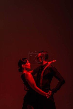 Photo pour Couple sensuel de danseurs exécutant tango sur fond sombre avec éclairage rouge - image libre de droit
