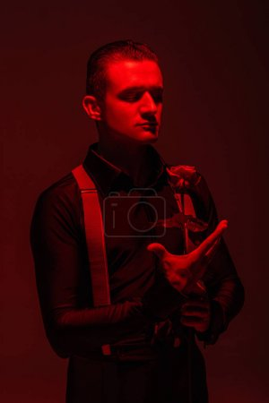 Photo pour Elegant tango dancer holding red rose on dark background with red lighting - image libre de droit