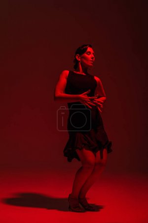 Photo pour Passionate dancer in black dress performing tango on dark background with red lighting - image libre de droit