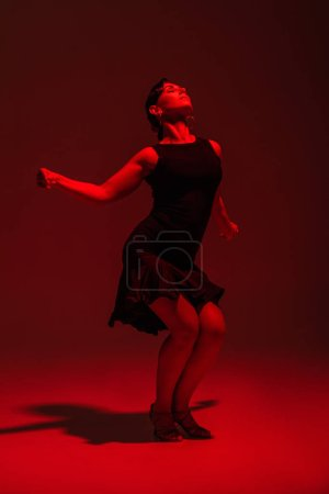 Photo for Sensual dancer in black dress performing tango on dark background with red lighting - Royalty Free Image