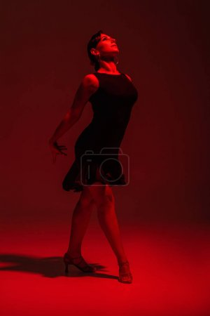 Photo for Beautiful dancer in black dress performing tango on dark background with red lighting - Royalty Free Image