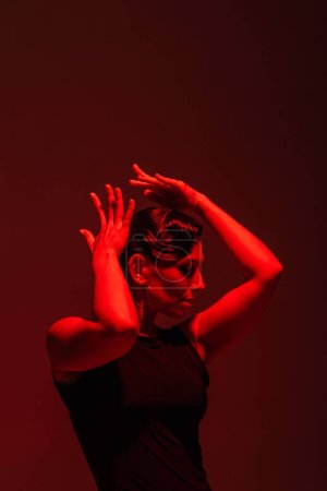 Photo pour Expressive dancer performing tango on dark background with red lighting - image libre de droit