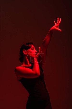 Photo pour Belle danseuse en robe noire jouant du tango sur fond sombre avec illumination rouge - image libre de droit