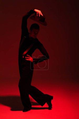 Photo pour Élégant danseur tenant chapeau au-dessus de la tête tout en effectuant tango sur fond sombre avec éclairage rouge - image libre de droit