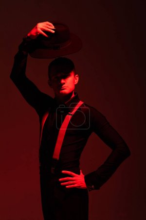 Photo pour Expressive tango dancer looking at camera and holding hat above head on dark background with red lighting - image libre de droit