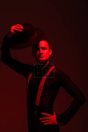 Photo pour Handsome tango dancer looking at camera and holding hat above head on dark background with red lighting - image libre de droit
