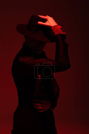 Photo for Expressive dancer in black clothing and hat performing tango on dark background with red illumination - Royalty Free Image