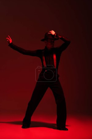 Photo pour Elegant dancer touching hat while performing tango on dark background with red illumination - image libre de droit
