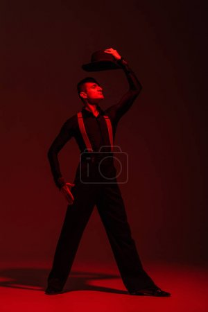 Photo for Stylish dancer holding hat above head while performing tango on dark background with red lighting - Royalty Free Image
