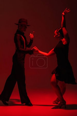 Photo for Elegant couple of dancers in black clothing performing tango on dark background with red illumination - Royalty Free Image