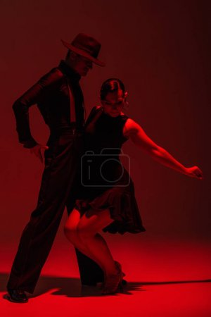 Photo pour Passionate couple of dancers in black clothing performing tango on dark background with red illumination - image libre de droit