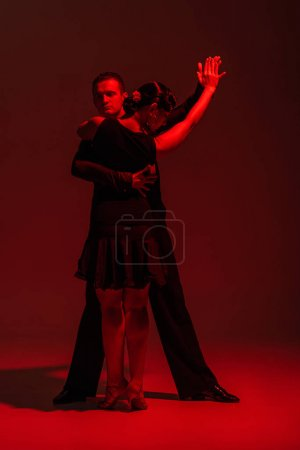 Photo pour Elegant couple of dancers in black clothing performing tango on dark background with red lighting - image libre de droit