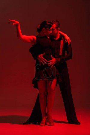 Photo pour Élégant couple de danseurs en vêtements noirs exécutant tango sur fond sombre avec éclairage rouge - image libre de droit