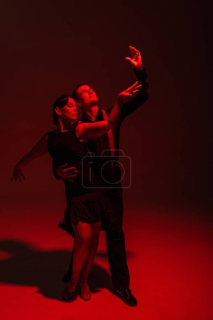 Photo pour Stlylish couple of dancers in black clothing performing tango on dark background with red illumination - image libre de droit