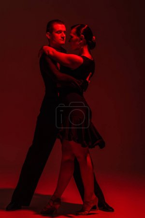 Photo pour Elegant couple of dancers performing tango on dark background with red illumination - image libre de droit