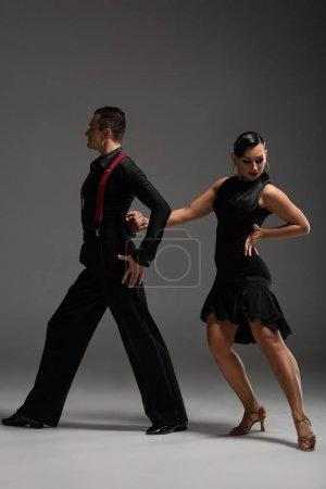 Photo pour Couple élégant de danseurs en vêtements noirs exécutant tango sur fond gris - image libre de droit