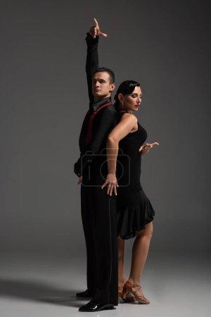 Photo pour Deux danseurs élégants en vêtements noirs exécutant le tango sur fond gris - image libre de droit