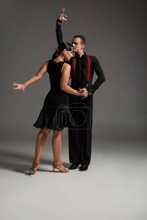 Photo pour Deux danseurs expressifs en vêtements noirs exécutant le tango sur fond gris - image libre de droit