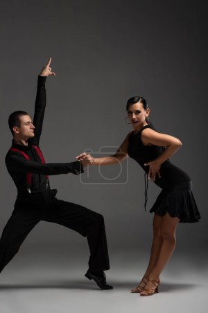 expressive couple of dancers in black clothing performing tango on grey background