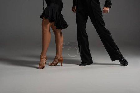 Photo pour Vue partielle de deux danseurs élégants en tenue noire exécutant le tango sur fond gris - image libre de droit