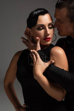 Photo for Sensual dancer hugging passionate partner while performing tango isolated on grey - Royalty Free Image