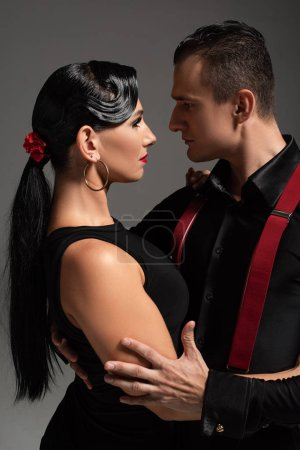 two passionate dancers performing tango face to face isolated on grey