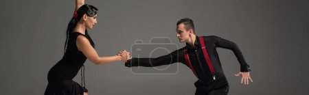 Photo pour Panoramic shot of sensual couple of dancers performing tango isolated on grey - image libre de droit