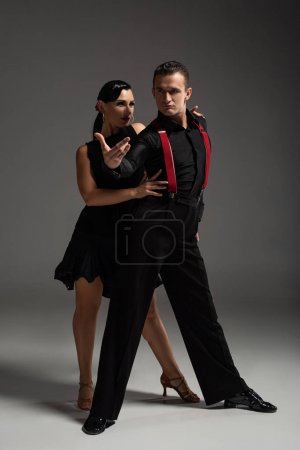 Photo pour Passionate couple of dancers in black clothing performing tango on grey background - image libre de droit