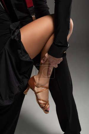 Photo pour Cropped view of tango dancer touching leg of partner on grey background - image libre de droit