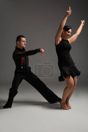 Photo for Sensual couple of dancers in black clothing performing tango on grey background - Royalty Free Image