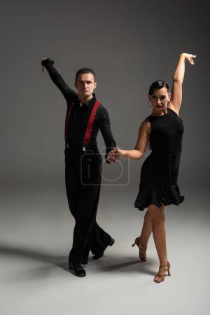 Photo pour Elegant dancers in black clothing looking at camera while dancing tango on grey background - image libre de droit