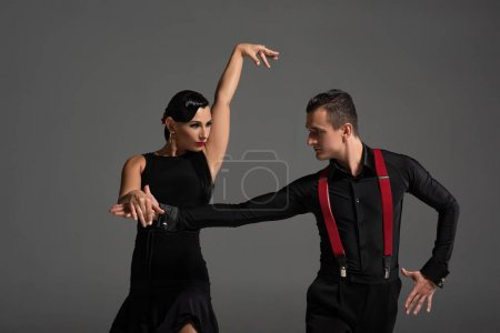 Photo pour Elegant couple of dancers looking at each other while performing tango isolated on grey - image libre de droit