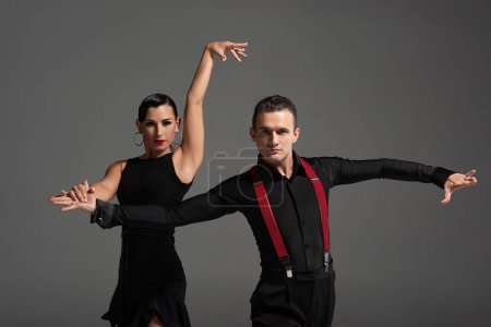 Photo pour Sensual couple of dancers looking at camera while performing tango isolated on grey - image libre de droit