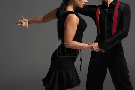 Photo pour Vue recadrée de danseurs élégants en vêtements noirs exécutant le tango isolé sur gris - image libre de droit