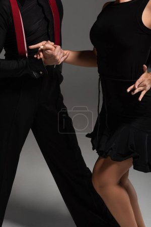 Photo pour Cropped view of dancers in black clothing performing tango on grey background - image libre de droit