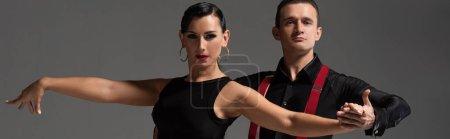 Photo pour Prise de vue panoramique de danseurs élégants en vêtements noirs regardant la caméra tout en exécutant le tango sur fond gris - image libre de droit