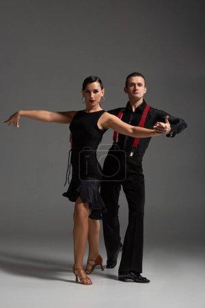 Photo pour Danseurs élégants en vêtements noirs regardant la caméra tout en effectuant tango sur fond gris - image libre de droit