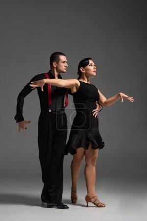 Photo pour Élégant couple de danseurs en vêtements noirs exécutant tango sur fond gris - image libre de droit