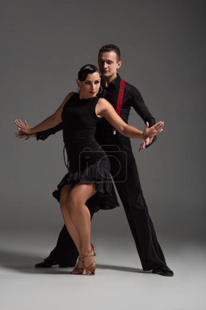 Photo for Sensual couple of dancers in black, elegant clothing performing tango on grey background - Royalty Free Image