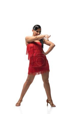 Photo pour Danseur expressif regardant loin et pointant du doigt tout en exécutant le tango sur fond blanc - image libre de droit